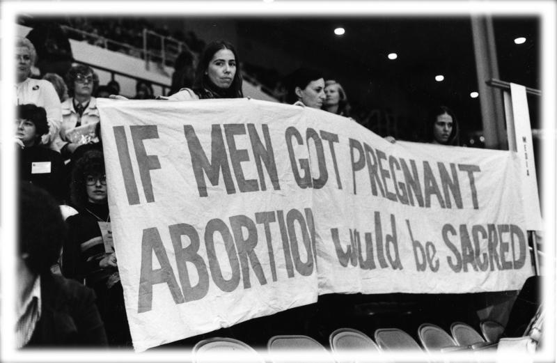 In the grandstand at the 1977 National Women's Conference, a group of women attendees hold a banner that reads 'If Men Got Pregnant Abortion Would Be Sacred,' Houston, Texas, November 1977. (Photo: National Commission for the Observance of the International Women's Year/PhotoQuest/Getty Images; digitally enhanced by Yahoo News)