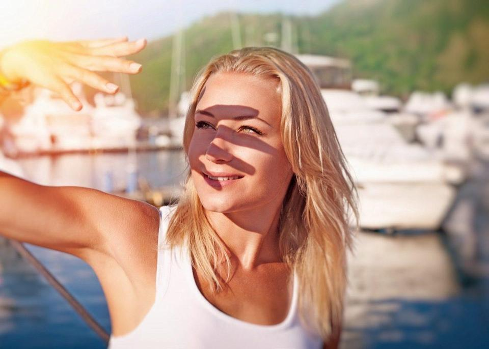 Woman covering face by hand of bright sun light.