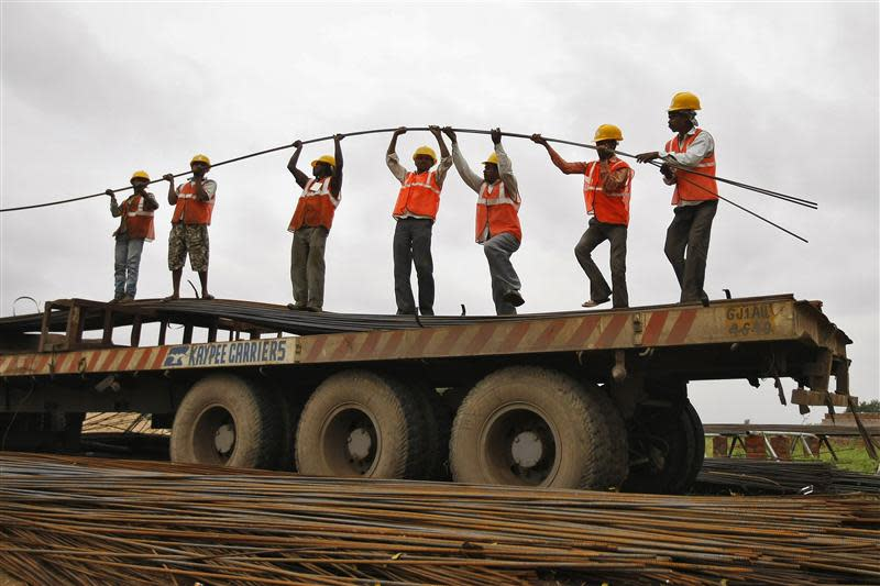 Workers unload iron rods from a truck at the construction site of an educational institute on the outskirts of Ahmedabad