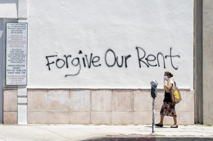 A woman wearing a mask walks past a wall bearing a graffiti asking for rent forgiveness on La Brea Ave on National May Day amid the Covid-19 pandemic, May 1, 2020, in Los Angeles, California. (Photo by VALERIE MACON / AFP)
