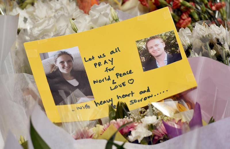 A card shows photos of Katrina Dawson (L) and Tori Johnson (R) - the two hostages killed during a fatal siege in the heart of Sydney's financial district - sitting amongst flowers at a makeshift memorial near the scene on December 17, 2014 (AFP Photo/William West)