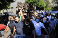 Mourners carry the coffin of Ibrahim Harb, 35, who was critically injured in the massive explosion at Beirut's port last year and who died on Monday nearly 14 months after the blast, during his funeral procession, in Beirut, Lebanon, Tuesday, Sept. 28, 2021. On Aug. 4, 2020, hundreds of tons of ammonium nitrate, a highly explosive material used in fertilizers, ignited after a massive fire at the port. The death brings to at least 215 the number of people who have been killed by the blast, according to official records. (AP Photo/Hussein Malla)