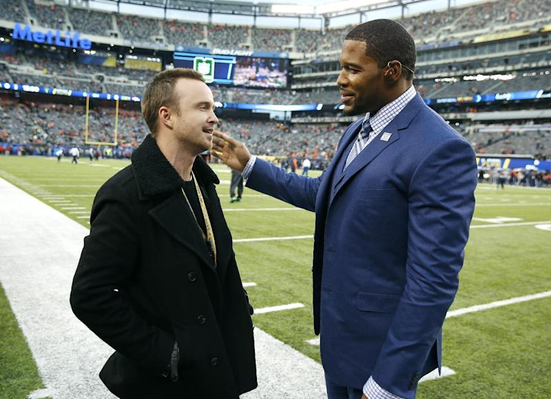 Actor Aaron Paul, left, talks to former NFL football player Michael Strahan before the NFL Super Bowl XLVIII football game between the Seattle Seahawks and the Denver Broncos, Sunday, Feb. 2, 2014, in East Rutherford, N.J. (AP Photo/Evan Vucci)