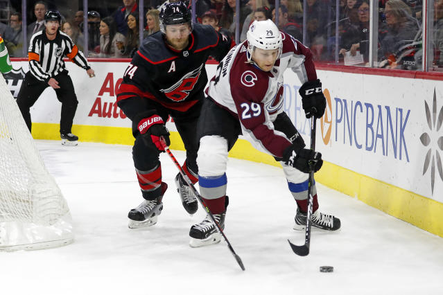 Colorado Avalanche's Nathan MacKinnon (29) vies with Carolina Hurricanes' Jaccob Slavin (74) for the puck during the first period of an NHL hockey game in Raleigh, N.C., Friday, Feb. 28, 2020. (AP Photo/Karl B DeBlaker)