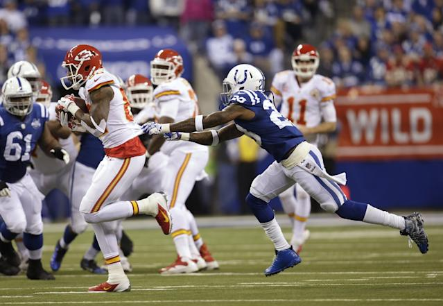 Kansas City Chiefs wide receiver Dwayne Bowe (82) runs out of the grasp of Indianapolis Colts cornerback Greg Toler (28) during the first half of an NFL wild-card playoff football game Saturday, Jan. 4, 2014, in Indianapolis. (AP Photo/AJ Mast)