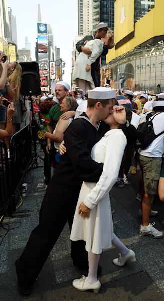Couples, some dressed as sailors and nurses, embrace in Times Square on August 14, 2015, in New York (AFP Photo/Don Emmert)