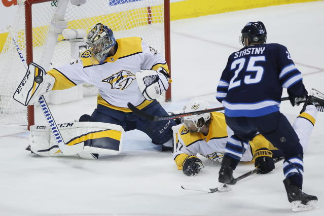 A shot by Winnipeg Jets' Paul Stastny (25) is stopped by Nashville Predators goaltender Pekka Rinne (35) as Scott Hartnell (17) defends during the first period of Game 4 of an NHL hockey second-round playoff series in Winnipeg, Manitoba, Thursday, May 3, 2018. (John Woods/The Canadian Press via AP)