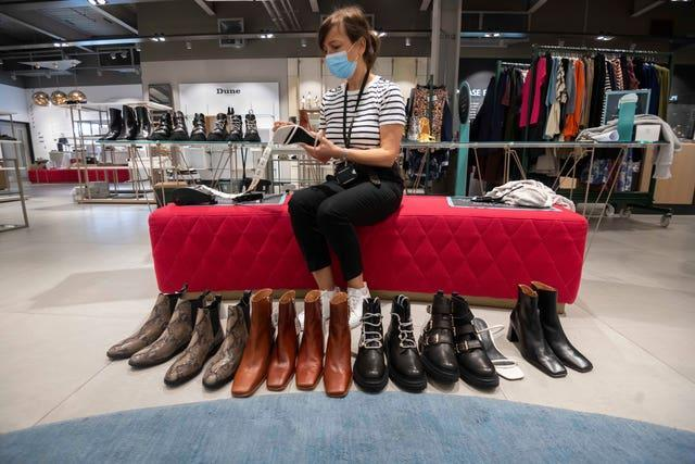 A staff member cleaning shoes at the John Lewis White City store ahead of reopening (Paul Grover/PA)