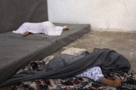 The daughter (bottom) of Tunisian Iman Othman, wife of a former Islamic State fighter, is covered against flies while she sleeps at a camp for displaced people in Ain Issa, north of Raqqa, Syria June 21, 2017. Picture taken June 21, 2017. REUTERS/Rodi Said
