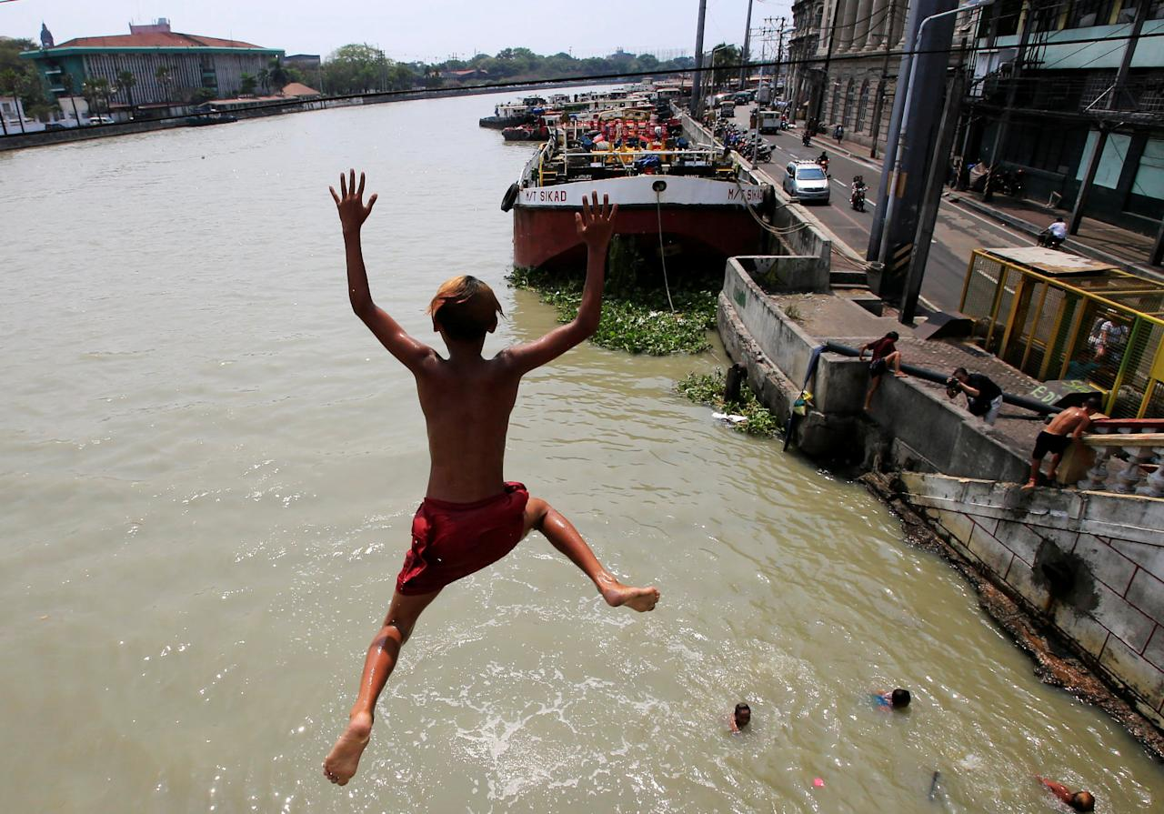 A teenager dives into the polluted water of Manila Bay ahead of World Water Day in Binondo, Metro Manila, Philippines March 21, 2018. REUTERS/Romeo Ranoco