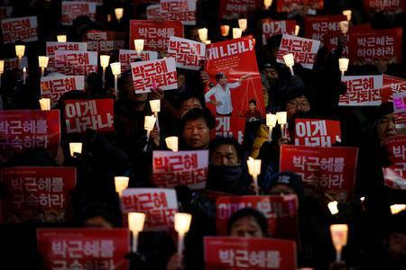 """People chant slogans during a protest calling for South Korean President Park Geun-hye to step down in central Seoul, South Korea, November 29, 2016. The sign reads """"Step down Park Geun-hye immediately"""". REUTERS/Kim Hong-Ji"""