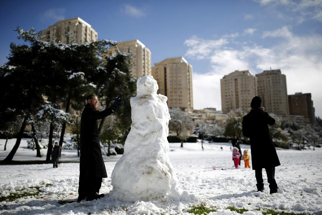 An ultra-Orthodox Jewish man builds a snowman in Jerusalem December 12, 2013. Schools and offices in Jerusalem and parts of the occupied West Bank were closed and public transport briefly suspended after heavy snowfall on Thursday. REUTERS/Amir Cohen (JERUSALEM - Tags: ENVIRONMENT)
