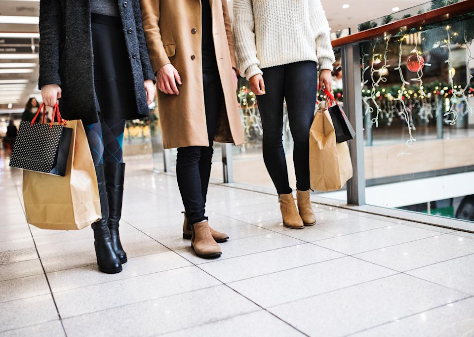 Unrecognizable young friends with bags walking in shopping center at Christmas time.