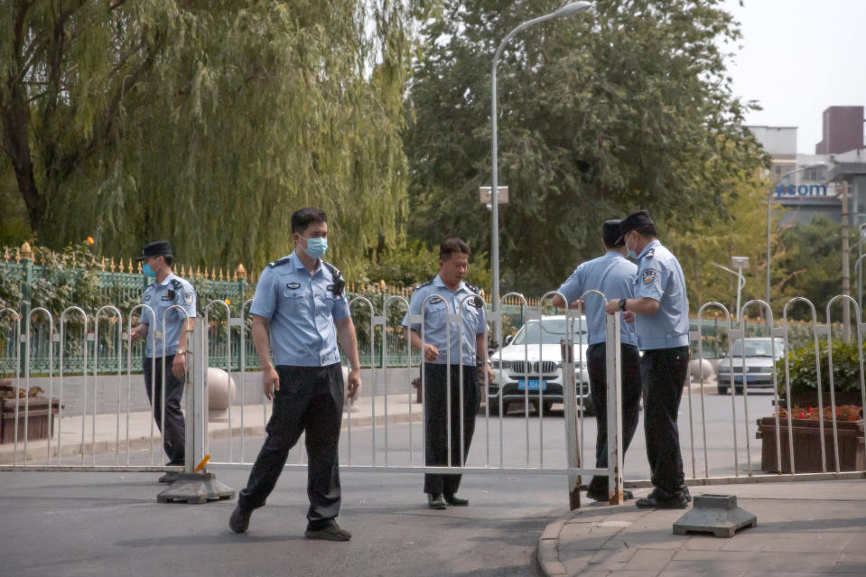 Police officers pull a barricade across a road leading to the a residential neighborhood near the Xinfadi wholesale food market district in Beijing, Saturday, June 13, 2020. Beijing closed the city's largest wholesale food market Saturday after the discovery of seven cases of the new coronavirus in the previous two days. (AP Photo/Mark Schiefelbein)