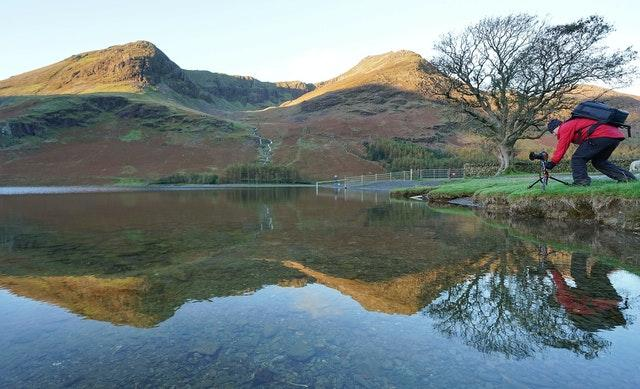 A photographer lines up his shot of autumn reflections in lake Buttermere in the Lake District, Cumbria