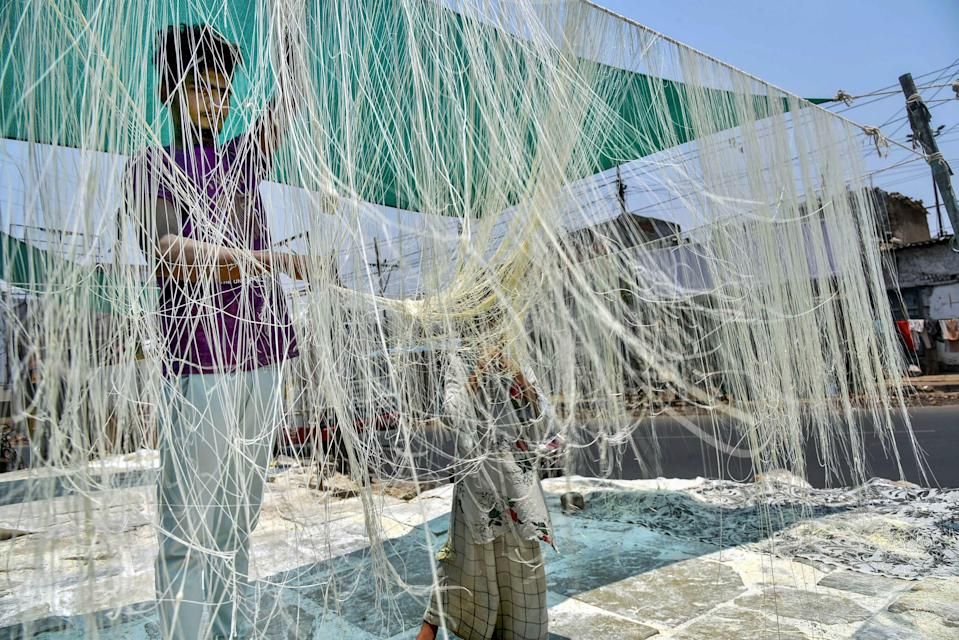 A worker dries handmade vermicelli, considered as one of the delicacies during Ramzan, in Hyderabad, Thursday, 29 April 2021.
