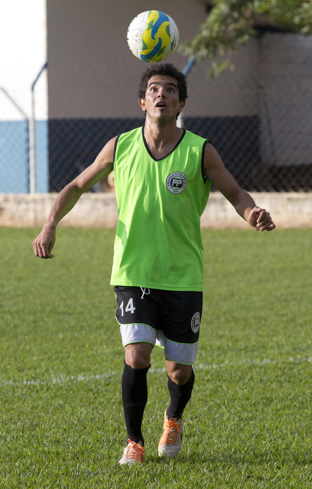 """In this May 28, 2014 photo, Rogerio Salvato Jr., who plays with the Presidente Prudente soccer club, trains in Presidente Prudente, Brazil. """"I wouldn't be able to provide for my family only by playing football,"""" he said. """"... I make more money by delivering takeout than I do by playing football."""" (AP Photo/Andre Penner)"""