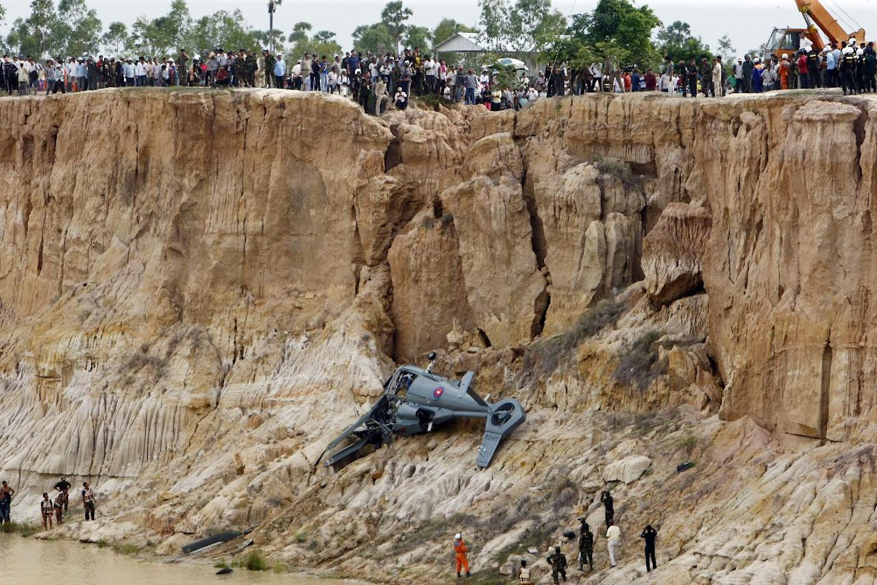 Soldiers use a crane to lift an aft section of a helicopter retrieved from a pond following its crash in Prey Sar village at the outskirt of Phnom Penh, Cambodia, Monday, July 14, 2014. The chopper went down about 10 kilometers (6 miles) south of Phnom Penh on Monday, sinking in a muddy pond surrounded by rural land and rice fields. (AP Photo/Heng Sinith)