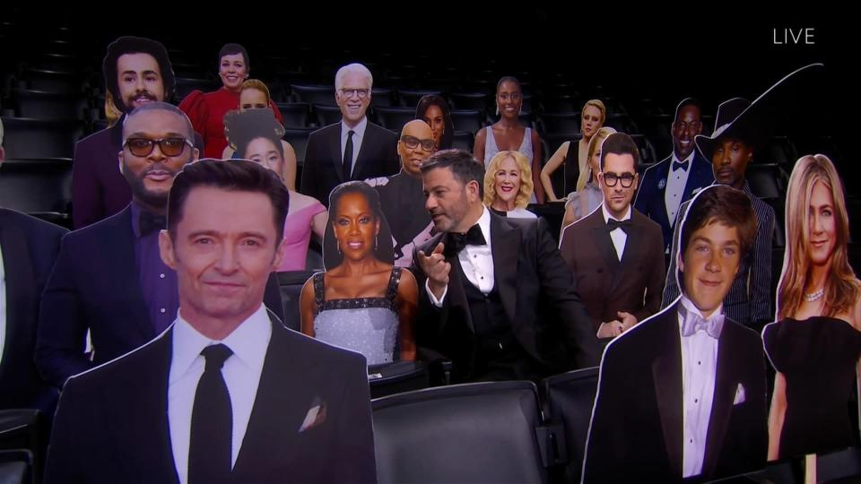 This image released by the Television Academy shows host Jimmy Kimmel, center, chatting with a cardboard cut-out of Regina King while surrounded by other celebrity cut-outs during the 72nd Emmy Awards telecast on Sept. 20, 2020 (Invision for the Television Academy via AP)