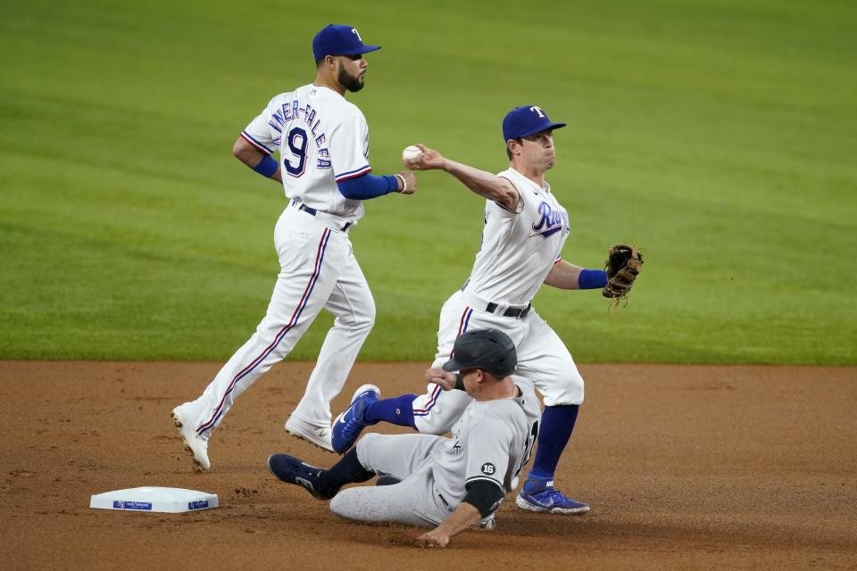 Texas Rangers shortstop Isiah Kiner-Falefa, left, looks on as second baseman Nick Solak, right, throws to first after forcing New York Yankees' Brett Gardner, center, at second to complete the double play against Aaron Judge in the first inning of a baseball game in Arlington, Texas, Tuesday, May 18, 2021. (AP Photo/Tony Gutierrez)