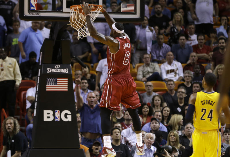 Miami Heat's LeBron James dunks as Indiana Pacers' Paul George (24) watches during the first half of an NBA basketball game, Wednesday, Dec. 18, 2013, in Miami. (AP Photo/Lynne Sladky)