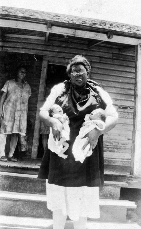 """A Florida midwife holds twins in this undated photo. Black midwives in the South continued delivering babies for disadvantaged women in rural communities until well into the 1970s, despite a campaign by modern gynecologists to portray them as superstitious and unfit. <span class=""""copyright"""">(Florida Memory)</span>"""