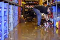 Louis Dearani, Jr., right, helps to clean up after his family business, United Automatic Fire Sprinkler, was flooded from the remnants of Hurricane Ida that hit the area in Woodland Park, N.J., Thursday, Sept. 2, 2021. (AP Photo/Seth Wenig)