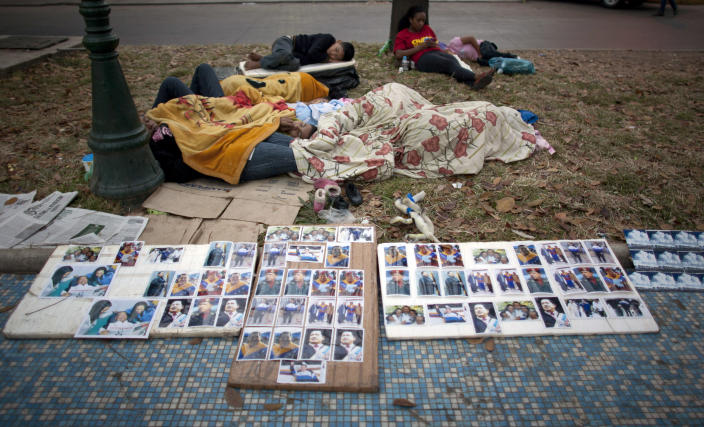 People rest outside the military academy where Venezuela's late President Hugo Chavez is lying in state in Caracas, Venezuela, early Sunday, March 10, 2013. People continue to parade to see the body of Chavez, who died of cancer on March 5. (AP Photo/Ariana Cubillos)