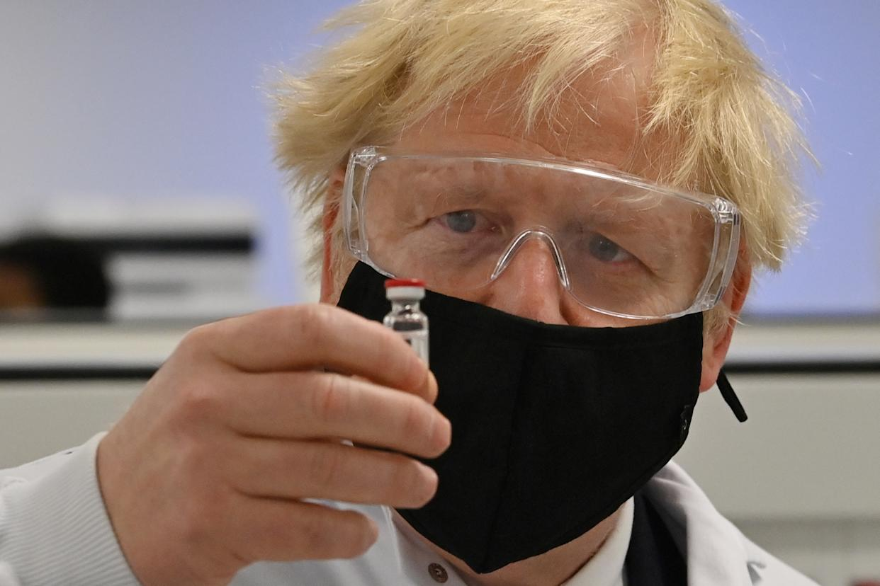 WREXHAM, WALES - NOVEMBER 30: UK Prime Minister Boris Johnson poses for a photograph with a vial of the AstraZeneca/Oxford University COVID-19 candidate vaccine, known as AZD1222, at Wockhardt's pharmaceutical manufacturing facility on November 30, 2020 in Wrexham, Wales.  The UK government announced a deal in August with global pharmaceutical and biotechnology company Wockhardt, to increase capacity in a crucial part of the manufacturing process for Covid-19 vaccines. Britain has been Europe's worst-hit country during the pandemic, recording more than 57,000 deaths from some 1.6 million cases.  (Photo by Paul Ellis - WPA Pool/Getty Images)