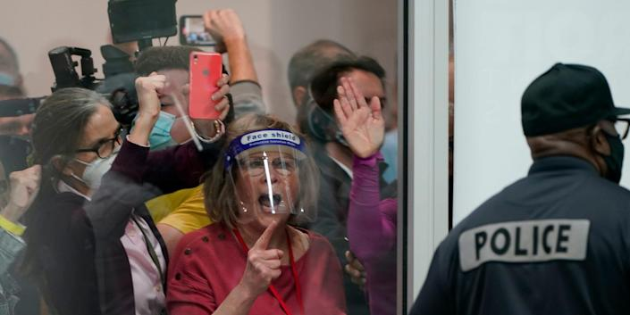 Surplus election challengers yell behind windows at the central counting board in Detroit, Michigan
