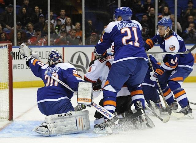 New Jersey Devils' Adam Henrique (14) shoots the puck past New York Islanders goalie Evgeni Nabokov (20) as Islanders' Kyle Okposo (21) and Calvin de Haan (44) watch from behind in the first period of an NHL hockey game on Saturday, March 1, 2014, in Uniondale, N.Y. (AP Photo/Kathy Kmonicek)