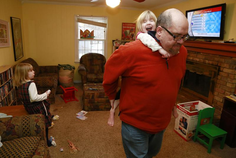 Mike Beck carries his daughter Veronica on his back through the family's living room as his daughter Maria, left, plays a video while trying to combat cabin fever, Monday, Feb. 3, 2014, in Indianapolis. (AP Photo/R Brent Smith)