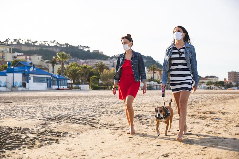 Two friends walking on the beach with dog during covid epidemic. (Photo: LeoPatrizi via Getty Images)