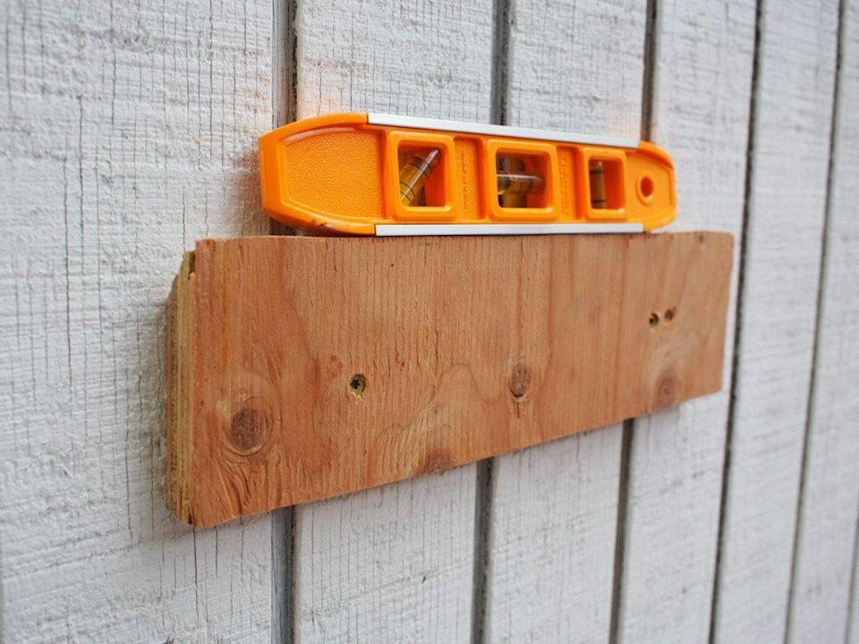 <p>Use a level and attach the long plywood cleat to the wall using wood screws. It's best to install the cleat into studs which are typically 16 inches to 24 inches apart. </p>