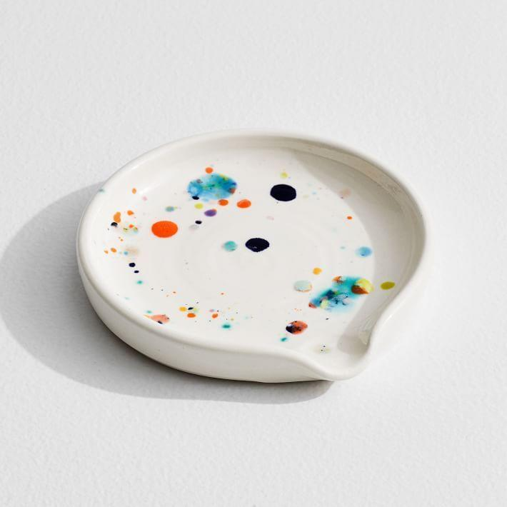 """<p><strong>A MANO</strong></p><p>westelm.com</p><p><strong>$34.00</strong></p><p><a href=""""https://go.redirectingat.com?id=74968X1596630&url=https%3A%2F%2Fwww.westelm.com%2Fproducts%2Flcl-louisa-podlich-confetti-spoo-rest-d7950&sref=https%3A%2F%2Fwww.redbookmag.com%2Flife%2Fg36197361%2Fhousewarming-gifts%2F"""" rel=""""nofollow noopener"""" target=""""_blank"""" data-ylk=""""slk:BUY NOW"""" class=""""link rapid-noclick-resp"""">BUY NOW</a></p><p>A pretty spoon rest adds personality and functionality to the homeowner's brand new kitchen—and all of the special occasion meals to come.</p>"""