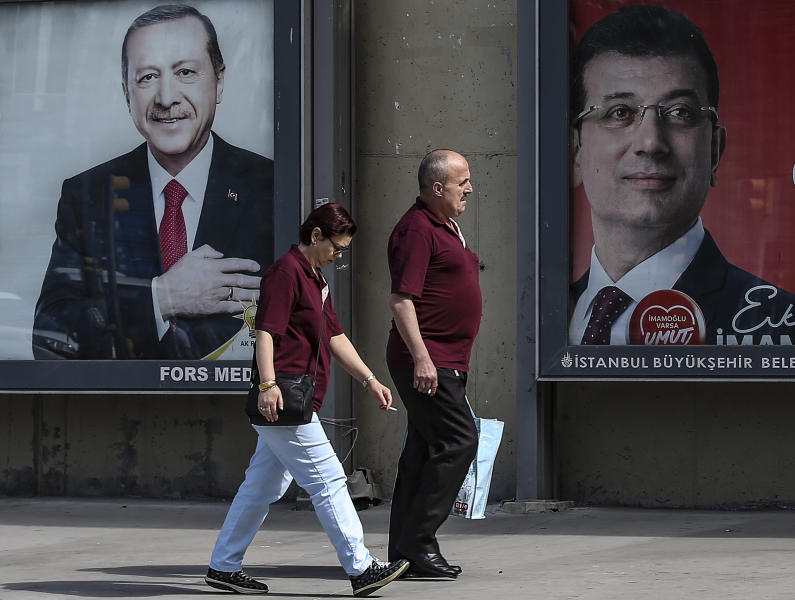 In this Tuesday, June 4, 2019 photo, people walk past posters of Turkey's President Recep Tayyip Erdogan, left, and Ekrem Imamoglu, right, Istanbul's mayoral candidate of the secular opposition Republican People's Party, or CHP, ahead of June 23 re-run of Istanbul elections, in Istanbul. Imamoglu, the 49-year-old candidate won the March 31 local elections with a slim majority, but after weeks of recounting requested by the ruling party, Turkey's electoral authority annulled the result of the vote, revoked his mandate and ordered the new election. (AP Photo/Emrah Gurel)
