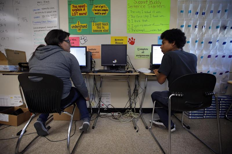 """Mariah Arostigue, left, and Noah Reyes, 11th graders, chat as they work on their homework in a pre-calculus class at Segerstrom High School in Santa Ana, Calif., Wednesday, Jan. 16, 2013. A growing number of teachers are implementing what is known as """"flipped learning,"""" in which students learn lessons as homework, mostly through online videos produced by teachers, and use classroom time to practice what they learned. (AP Photo/Jae C. Hong)"""