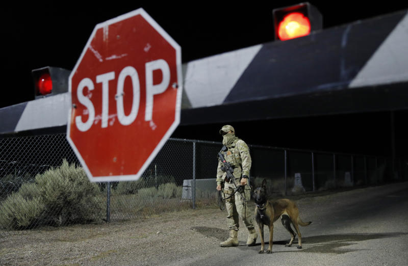 """A security guard stands at an entrance to the Nevada Test and Training Range near Area 51 Friday, Sept. 20, 2019, near Rachel, Nev. People gathered at the gate inspired by the """"Storm Area 51"""" internet hoax. (AP Photo/John Locher)"""