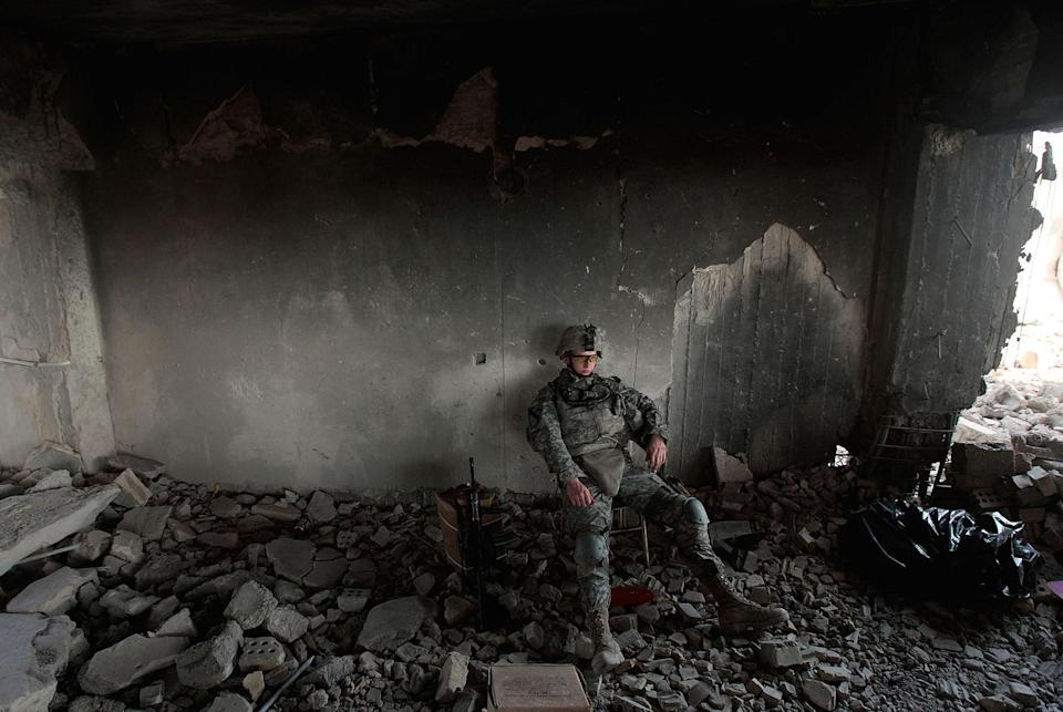 <p>Pft. Daniel Sims of Clemson, South Carolina of the 1st Battalion, 5th Cavalry Regiment of the U.S. Army sits during watch duties in a partially destroyed building that's being converted to an Army field post July 13, 2007 in the tense Amariyah neighborhood of Baghdad, Iraq. Insurgents who were in control of Amariyah until recently attempted to destroy this building and an adjacent bunker with explosives and burning tires, but the Army was able to salvage the compound and is now occupying it. (Photo by Chris Hondros/Getty Images) </p>