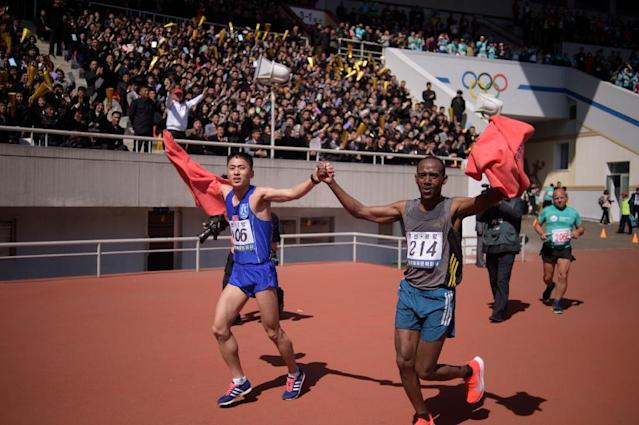 Ri Kang Bom (L) of North Korea runs with a competitor from Ethiopia after crossing the finish line of the annual race (AFP Photo/KIM Won Jin )