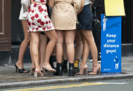 FILE - In this Saturday July 4, 2020 file photo women gather outside a bar in Manchester, England. England is embarking on perhaps its biggest lockdown easing yet as pubs and restaurants have the right to reopen for the first time in more than three months. (AP Photo/Jon Super, File)