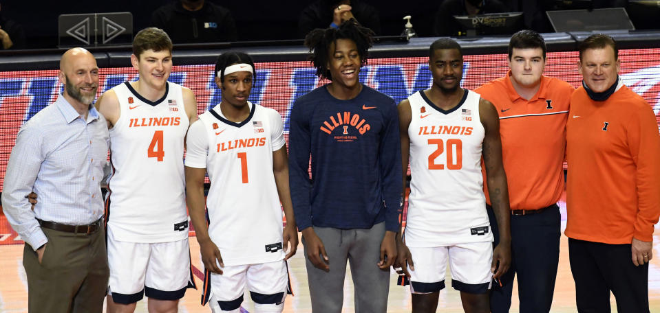Illinois' Ayo Dosunmu, center, stands with teammates and athletic director Josh Whitman, left, and coach Brad Underwood, right, before the team's last home game of the NCAA college basketball season, against Nebraska on Thursday, Feb. 25, 2021, in Champaign, Ill. Dosunmu missed the game because of a broken nose. (AP Photo/Holly Hart)