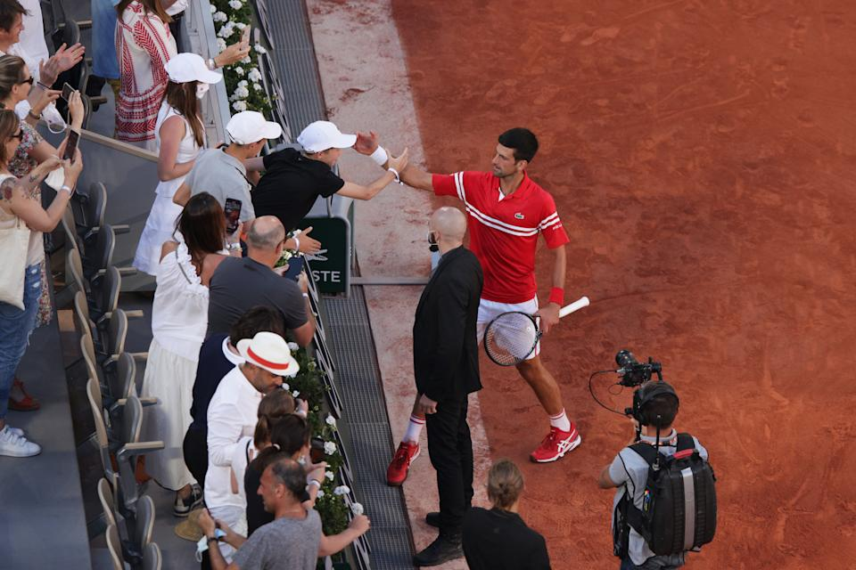 Tournament winner Novak Djokovic (pictured right) celebrates with a fan after winning his Men's Singles Final match at Roland Garros on June 13, 2021 in Paris, France.