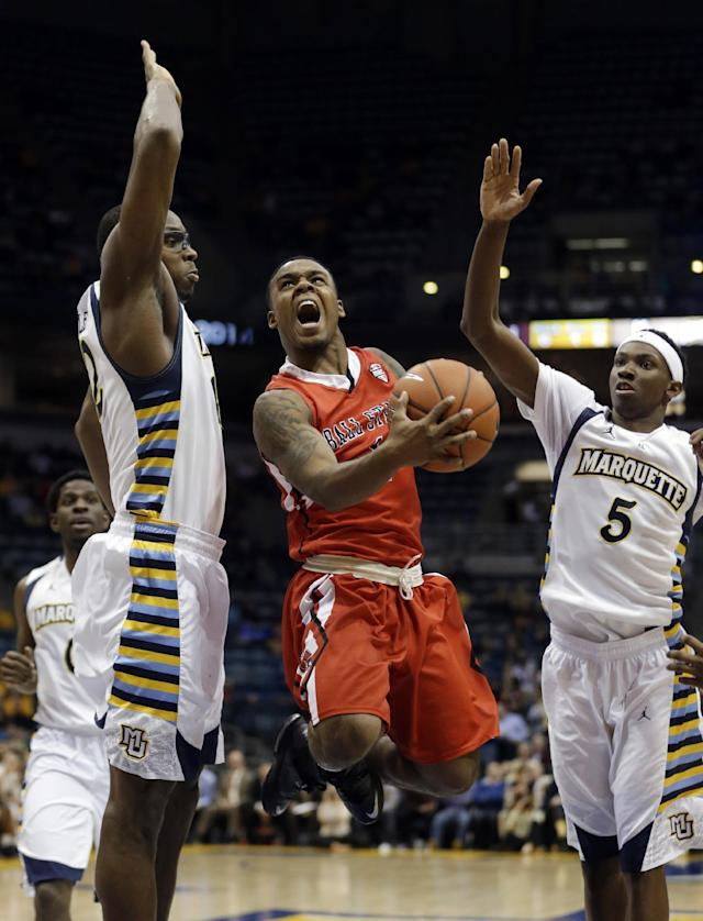 Ball State's Zavier Turner tries to drive between Marquette's John Dawson and JaJuan Johnson (5) during the second half of an NCAA college basketball game Tuesday, Dec. 17, 2013, in Milwaukee. (AP Photo/Morry Gash)