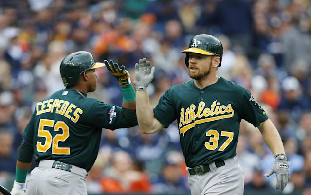 Oakland Athletics' Brandon Moss is greeted by Yoenis Cespedes after his solo home run during the fifth inning of Game 3 of an American League baseball division series against the Detroit Tigers in Detroit, Monday, Oct. 7, 2013. (AP Photo/Paul Sancya)