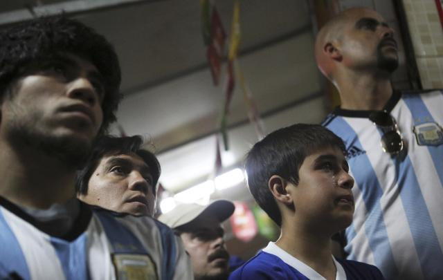 An Argentina fan (2nd R) cries as he watches the World Cup final match between Argentina and Germany, near Maracana stadium in Rio de Janeiro July 13, 2014. REUTERS/Nacho Doce (BRAZIL - Tags: SPORT SOCCER WORLD CUP)