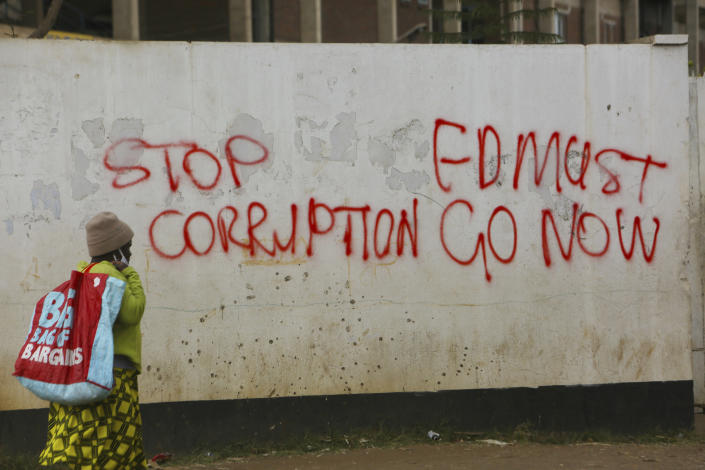 "A woman walks past a wall with graffiti calling on the government to stop corruption in this Monday, June, 15, 2020 photo. Unable to protest on the streets, some in Zimbabwe are calling themselves ""keyboard warriors"" as they take to graffiti and social media to pressure a government that promised reform but is now accused of gross human rights abuses.(AP Photo/Tsvangirayi Mukwazhi)"