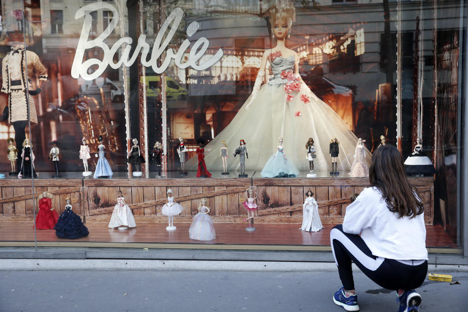 PARIS, FRANCE - DECEMBER 01: A woman wearing a protective face mask looks at various Barbie dolls on display in the window of a toy store for Christmas on December 01, 2020 in Paris, France. The reopening of stores selling