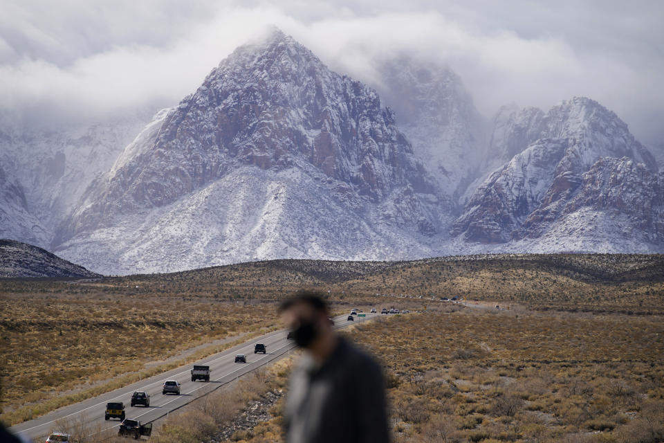 People look at mountains recently covered with snow, Monday, Jan. 25, 2021, at the Red Rock National Conservation Area near Las Vegas. (AP Photo/John Locher)