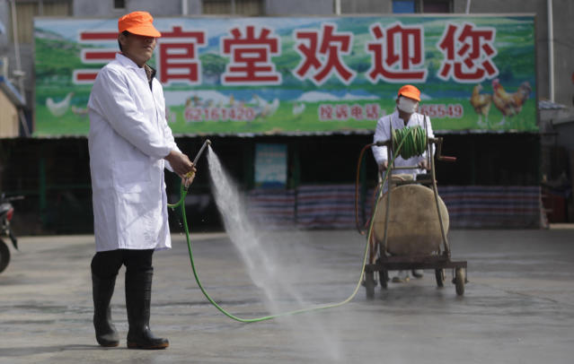 In this April 3, 2013 photo, workers disinfect at Sanguantang live poultry wholesale market in Shanghai, China. After a new and lethal strain of bird flu emerged in Shanghai two weeks ago, the government of China's bustling financial capital responded with live updates on a Twitter-like microblog. It's a starkly different approach than a decade ago, when Chinese officials silenced reporting as a deadly pneumonia later known as SARS killed dozens in the south. (AP Photo/Eugene Hoshiko)